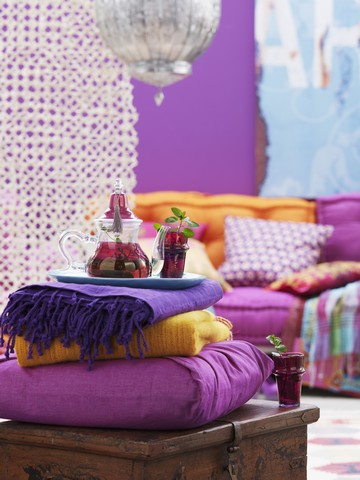 Orientalischer Farbklang - Decken, Kissen und Tablett mit gläserner Teekanne auf einer Holztruhe