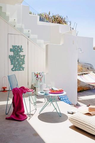 Terrassenbereich eines mediterranen weissen Wohnhauses mit Tisch & Stühlen aus Metall, Bodenkissen & Hängematte
